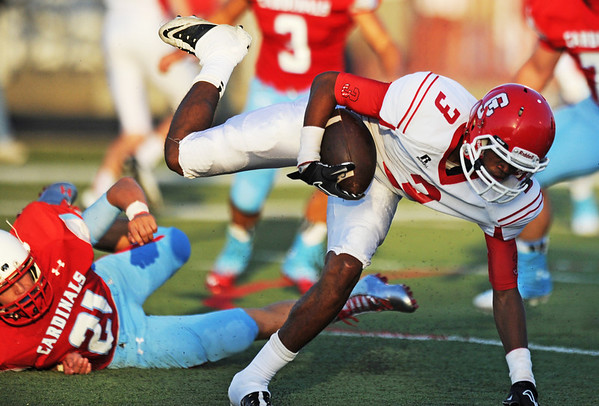Carl Junction's Matt Magee gets tripped up by Webb City's Kolesen Crane Friday night, Aug. 30, 2013, at Webb City's field.<br /> Globe | T. Rob Brown