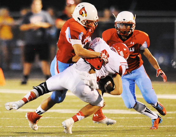 Webb City defensive back Austin Carter brings down Carl Junction receiver Tanner McMurtrey just after McMurtrey caught a pass Friday night, Aug. 30, 2013, at Webb City's field. Webb City teammate Roosevelt Edwards moves in to assist.<br /> Globe | T. Rob Brown