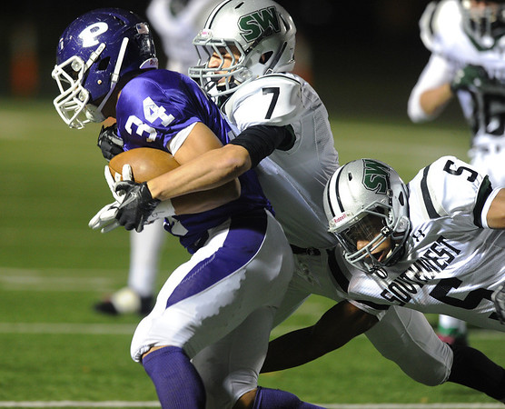 Globe/Roger Nomer<br /> Pittsburg's Alex Barnes is tackled by Blue Valley Southwest's Luke Wilmes (7) and Johnny Dunlap (5) during Friday's game.