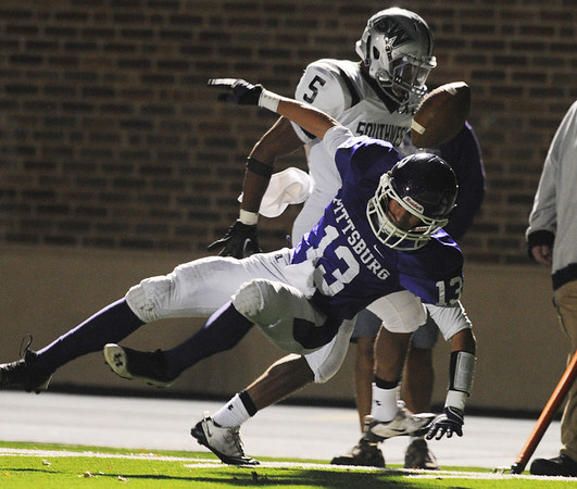 Globe/Roger Nomer<br /> A hit from Blue Valley Southwest's Johnny Dunlap knocks loose a pass intended for Pittsburg's Dante Richardson during Friday's game.