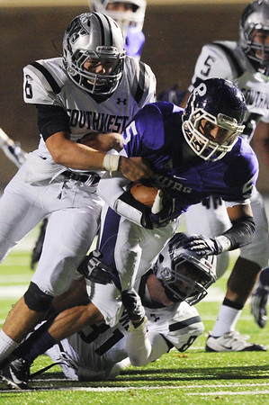 Globe/Roger Nomer<br /> Pittsburg's KJ Shaw is stopped by Blue Valley Southwest's Drake Herrman (6) and Sam Randall (81) during Friday's game.