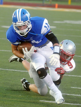 Globe/Roger Nomer<br /> Miller's Dylan Hill tackles McAuley's Greg Carney Friday at Fred G. Hughes Stadium.