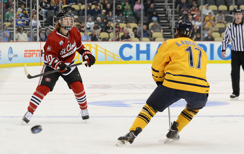 Tim Daly launches the puck past Quinnipiac's Jeremy Langlois.
