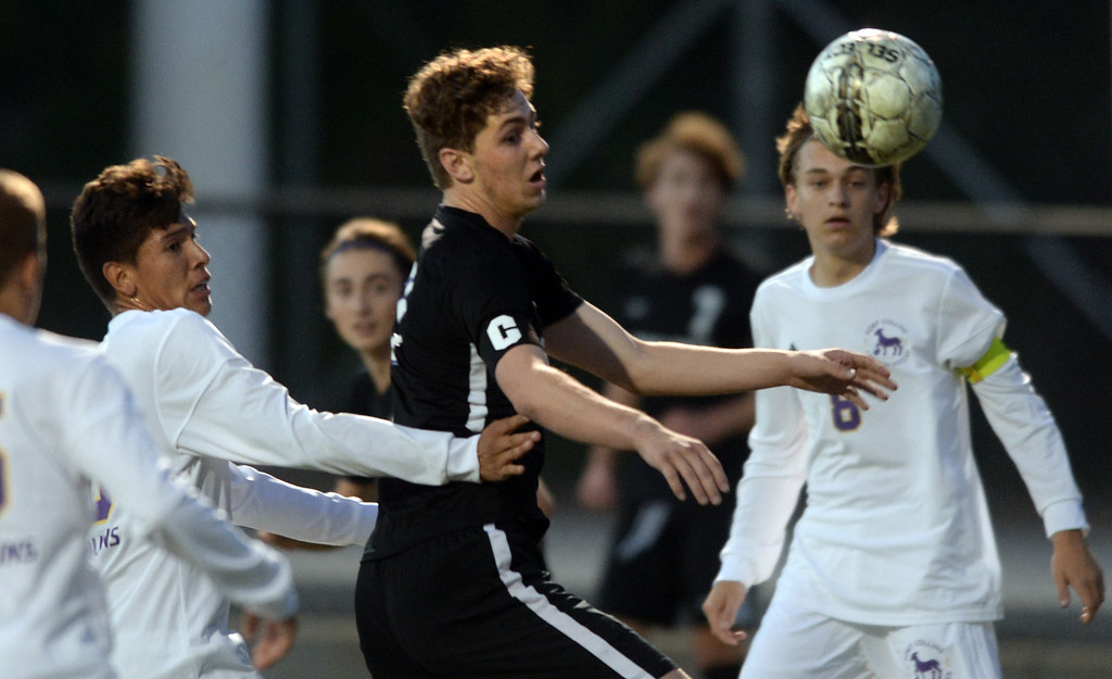 . BOULDER, CO - SEPTEMBER 13: Jesse Bacardi, center, of Boulder, run down the ball with Fernando Beltran, of Ft Collins, on the left. Boulder High played Ft Collins High at Recht Field on Thursday. (Photo by Cliff Grassmick/Staff Photographer)