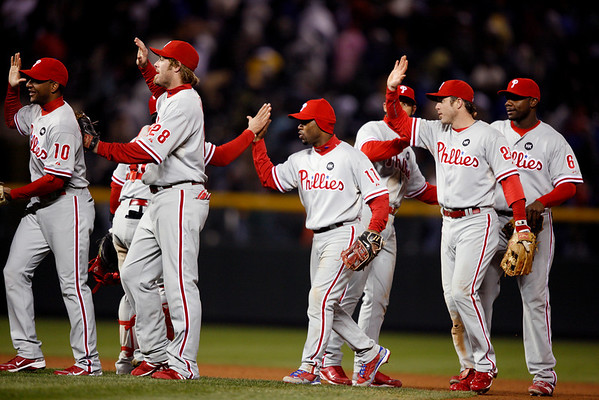 The Philadelphia Phillies celebrate after beating the Colorado Rockies 6-5 in Game 3 in a National League baseball division series in Denver on Sunday, Oct. 11, 2009. The win give the Phillies a 2-1 advantage in the series. (AP Photo/ Jack Dempsey)