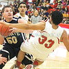 Santa Fe High Demon's, Isaiah Taylor #50 goes up for two points while  Bernalillo Spartan's Santiago Domingzue #33 gets pushed back while he tries to defend during the first quarter of their game at the Richard J. Kleoppel Gymnasium on Wednesday, February 19, 2014.  Jane Phillips/The New Mexican