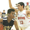 Santa Fe High Demon's , Keanyn Evans #22, goes up for two points while  Bernalillo Spartan's David Romero, #13, tries to defend during the first quarter of their game at the Richard J. Kleoppel Gymnasium on Wednesday, February 19, 2014.  Jane Phillips/The New Mexican