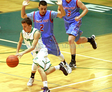 Pojoaque's Anthony Rodriguez, #11, dribbles down court while  Sandia Prep's  Johny Duran, #2 and Tyler Dorner, #3 try to defend during the third quarter of their game at the  Ben Lujan Gymnasium on Saturday, January 19, 2013.  Jane Phillips/The New Mexican