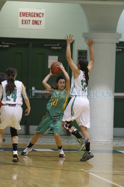 Mora's Destiny Pacheco, number 12, covers Pecos' Megan Armijo, number 10, during the fourth quarter of the Pecos vs Mora girl's basketball game of the Northern Rio Grande Tournament at Pojoaque High School on January 4, 2014. Luis Sanchez Saturno/The New Mexican