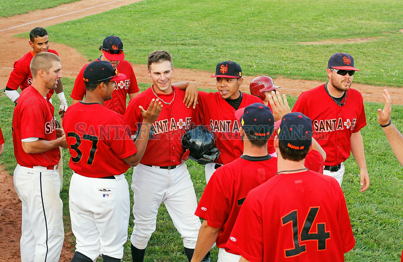 "Santa Fe Fuego's Aaron Carmen, #9, center, is congratulated by his team mates after he hit a home-run in the bottom of the fourth inning during their game against the  Raton Osos at Fort Marcy Ballpark on Tuesday, July 15, 2014.  Jane Phillips/The New Mexican  <a href=""http://tinyurl.com/omd3j4l"">http://tinyurl.com/omd3j4l</a>"