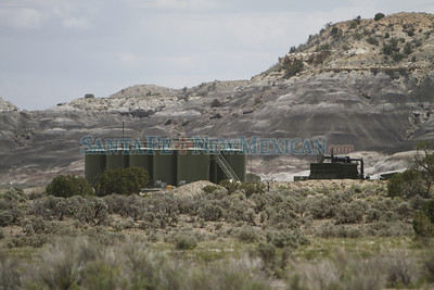 Crude oil tanks can be seen on Tuesday, June 17, 2014, with the black hills in the background where Georgia O'keeffe painted Black Place 2. Oil and gas drilling operations surround the Black Place where Georgia O'Keeffe painted iconic pieces depicting the black formations east of Nageezi. Some are calling for the area to be protected. Luis Sanchez Saturno/The New Mexican