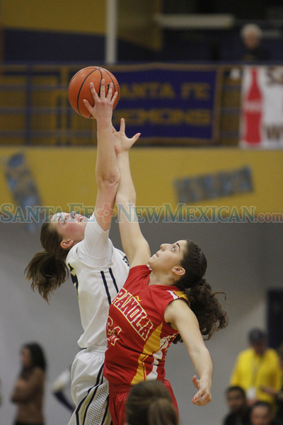 Santa Fe's Sabrina Lozada-Cabbage, number 25, and Española's Alexis Lovato, number 24, jump for the tip off at the begining of the first quarter of the Santa Fe High School vs Española High School at Santa Fe on Friday, February 28, 2014. Luis Sanchez Saturno/The New Mexican