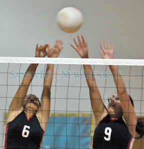 Lady Bobcats sophomore Tanisha Velasquez, left, and senior Amanda Villareal try to block a shot in Tuesday's match where McCurdy  High -vs- Dulce girls varsity volleyball match played at McCurdy, Tuesday, September 18, 2012. Clyde Mueller/The New Mexican