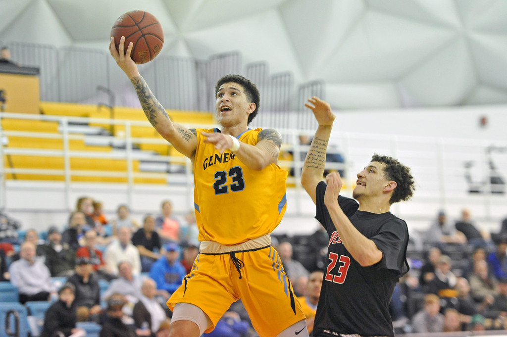 Mike Pruden | The Sheridan Press<br /> Channel Banks, left, scoops a layup past Western Wyoming's Nathan Fromm at the Bruce Hoffman Golden Dome Wednesday, Feb. 7, 2018. Banks finished with a game-high 27 points in Sheridan College's 76-71 win.