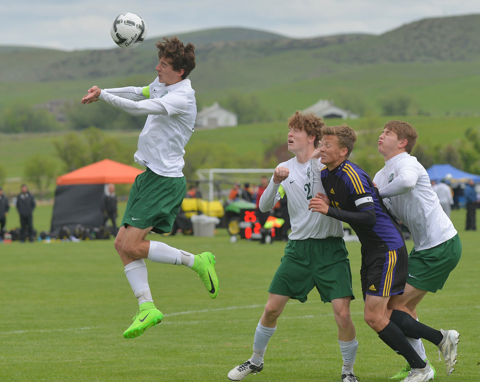 Justin Sheely | The Sheridan Press<br /> Kelly Walsh's Austin Kampa heads the ball as Ryan McMullen, Dalton Young and Joey Geil look on during the first round of the boys class 4A State Soccer Championship Thursday at the Big Horn Equestrian Center. The Trojans won in a shootout to advance to face Cheyenne Central in the semifinals on Friday.