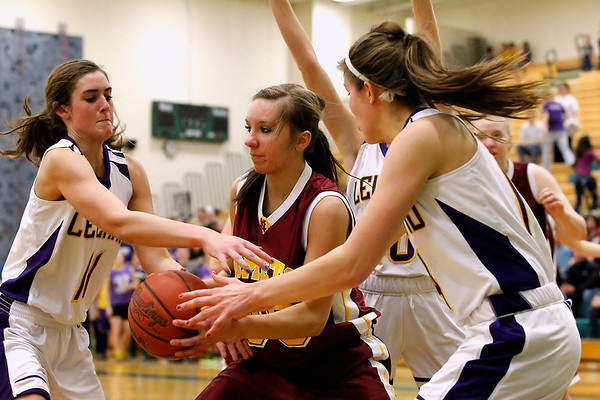Record-Eagle/Jan-Michael Stump<br /> Leland's Elizabeth McKee (11) and Tantzi Snyder (14) defend McBain NMC's Rachel Westmaas (30) in the first quarter of Thursday's game.