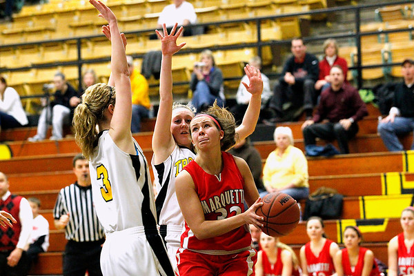 Record-Eagle/Jan-Michael Stump<br /> Marquette's Morgan Seibert (32) drives to the basket on Traverse City Central's Ali Walker (3) and Brianna Podsaid (1) in the third quarter of Wednesday's district semifinal.