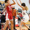 Goshen RedHawks senior Brynn Shoup-Hill (23) looks to pass the ball to her teammate against West Noble Chargers senior Lillian Mast (24) during Tuesday's game at West Noble High School in Ligonier.