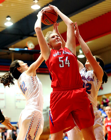 JAY YOUNG | THE GOSHEN NEWS<br /> West Noble senior Kaylie Warble (54) pulls down a rebound between Lakeland's Rebeka Stroop (12) and Elizabeth Stroop (22) during their sectional game Tuesday night at West Noble in Ligonier.