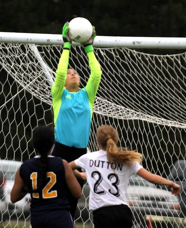 Record-Eagle/James Cook Northport goalie Joan Ogemaw makes a leaping save as Kingsley's Hannah Dutton and Northport's Manmeet Dhami (12) look on in Friday's game at Kingsley.
