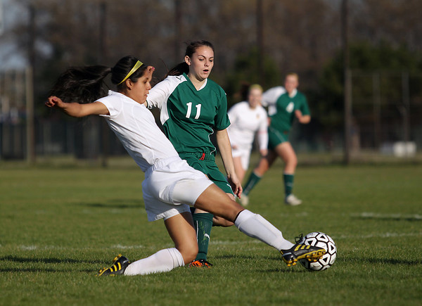 Record-Eagle/Keith King<br /> Traverse City Central's Jalyna Cisneros kicks the ball away from Traverse City West's Madison Jenner Tuesday, May 8, 2012 at the Coast Guard fields in Traverse City.