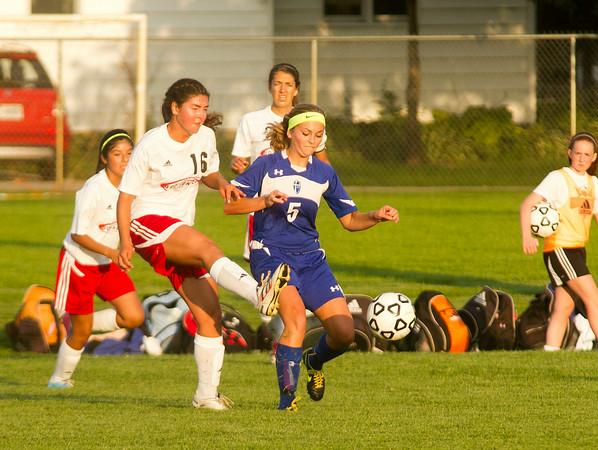 SAM HOUSEHOLDER   THE GOSHEN NEWS<br /> Goshen senior Jessica Oyer kicks the ball away from Mishawaka Marian player Gabby Lucchese Thursday during the game.