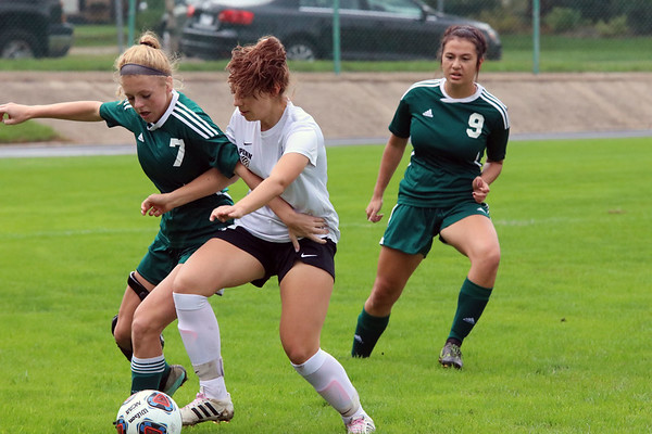 GREG KEIM | THE GOSHEN NEWS<br /> Junior Maddie Sorg of the Northridge Raiders and junior Allison Lankowicz of Penn battle for the ball in the IHSAA Class 3A girls soccer regional Saturday at Tallman-Beyrer Field in South Bend. Watching the play develop is No. 9 junior Mikayla Smith of the Raiders. Penn was a 4-0 winner.