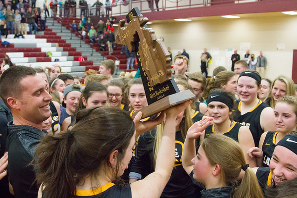 Record-Eagle/Brett A. Sommers Glen Lake head coach Jason Bradford passes the regional championship trophy to his team following Thursday's win over Charlevoix.