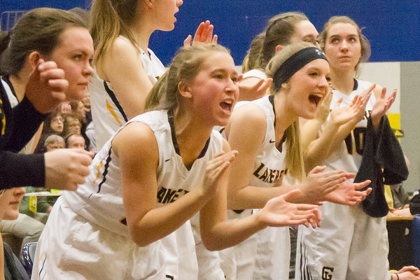 Record-Eagle/Brett A. Sommers <br /> <br /> Glen Lake's Lily Ewing (left) and Kasidy Skipski (right) cheer from the bench during Tuesday's Class C quarterfinal girls basketball game in Gaylord against St. Ignace. Glen Lake won 63-52.