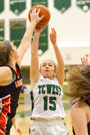 Record-Eagle/Brett A. Sommers Traverse City West's Sierra Perkette has her shot blocked by Ludington's Mackenzie Howe during Monday's girls basketball game against at TC West High School. TC West won 44-38.