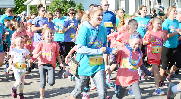 Will Fehlinger | The Herald-Tribune<br /> A wave of runners and walkers takes off from the starting line at the May 13 Girls on the Run spring 5K.