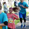 Will Fehlinger | The Herald-Tribune<br /> Runners trickle across the finish line after circling the Girls on the Run spring 5K route on May 13