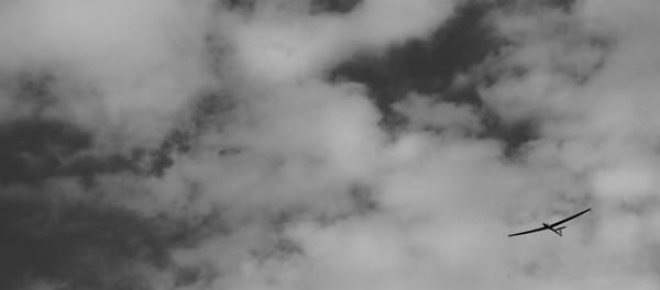 A lone glider in a cloudy sky