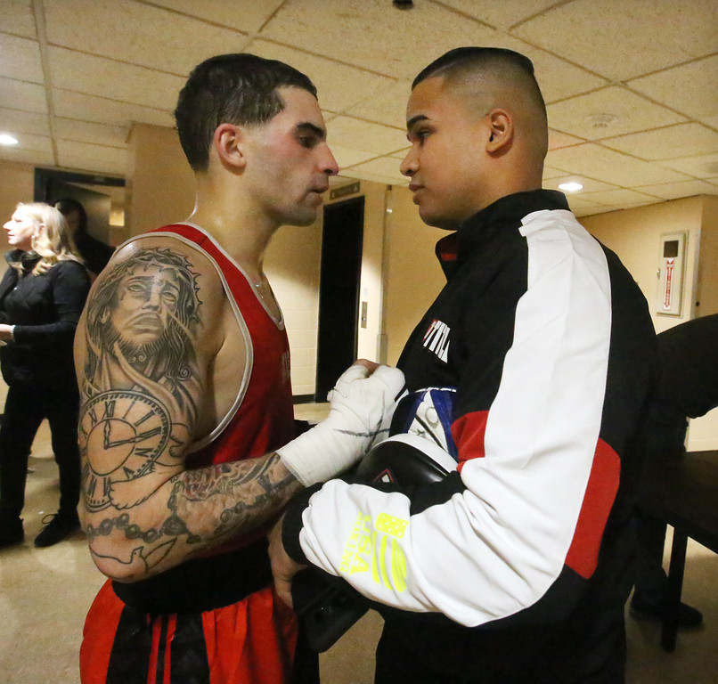 . Central/ Lowell Golden Gloves boxing. Preliminary bouts, Novice. Gabriel Morales of Dracut & Intenze 978 (Red corner), left, congratulated by teammate Andrew Perez of Methuen, who was boxing later in 201 lbs, after winning by unanimous decision over Gabriel Gerolomo in 141 lb Novice bout. (SUN/Julia Malakie)