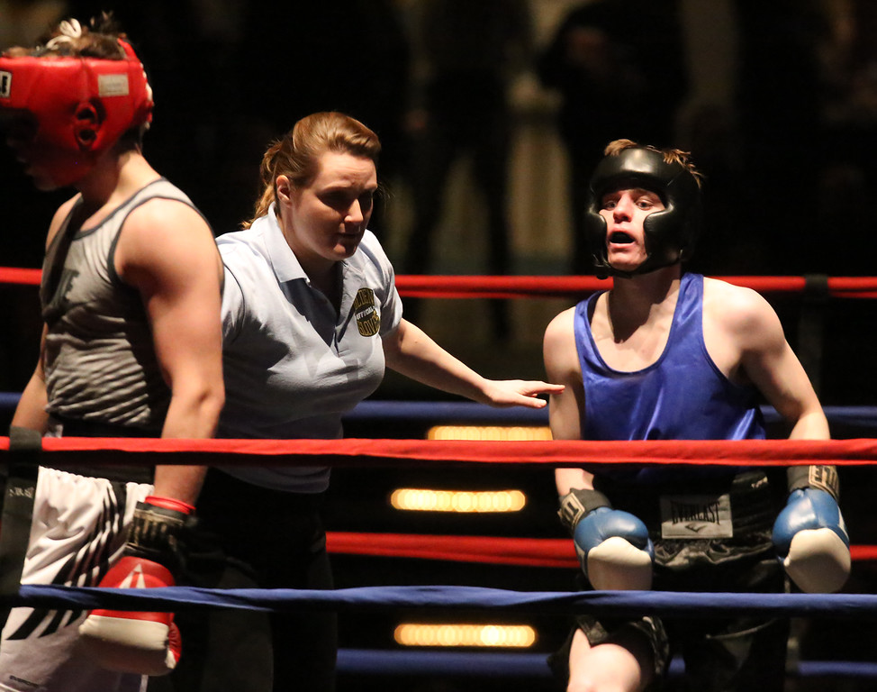 . Central/ Lowell Golden Gloves boxing. Preliminary bouts, Novice. Anthony Cefalo of South Boston & Peter Welch\'s Gym (Red corner), left, won in unanimous decision over Duncan McNeil of Groveland & Haverhill Downtown, seen here after getting up from the mat, in 141 lb Novice bout. Referee is Melissa Kelly. (SUN/Julia Malakie)