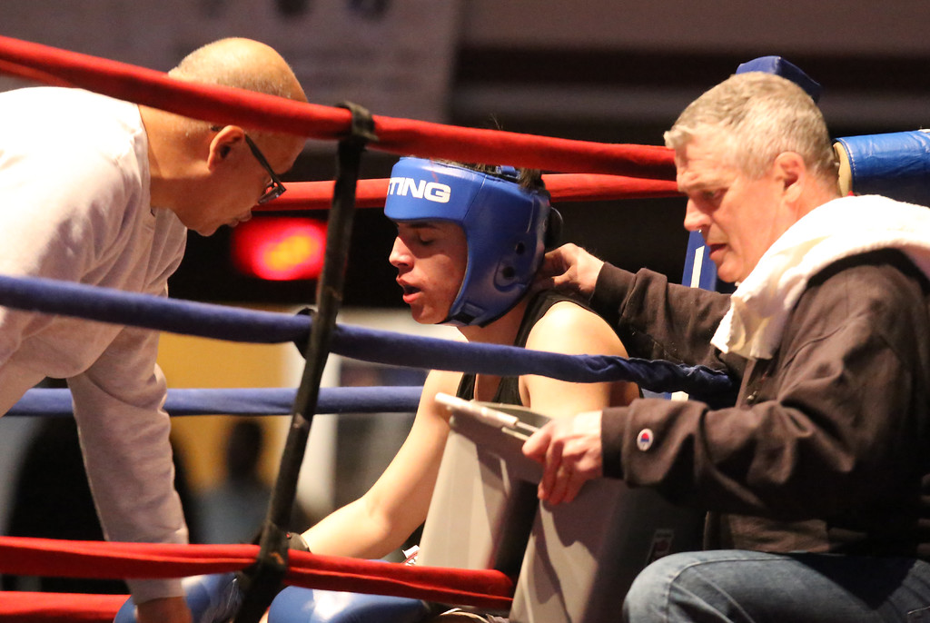 . Gabriel Gerolomo between rounds with trainer Dave Ortiz, left, Jackie O\'Neil of West End Gym. Central/ Lowell Golden Gloves boxing. Preliminary bouts, Novice. Gabriel Morales of Dracut & Intenze 978 (Red corner) won by unanimous decision over Gabriel Gerolomo of Lowell & Canal Street, in 141 lb Novice bout. (SUN/Julia Malakie)
