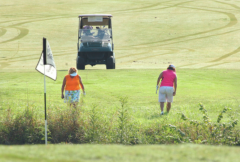Patti McCarver and Cindy Humphrey help look in the high grass for an errant shot from their three-some during the Executive Women's Golf Championship at the Cattails. Photo by ned Jilton II