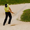 Greg Norman hitting out of the green side bunker on 17