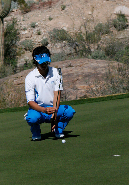 Yuta Iketa lines up a putt with the handle