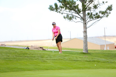 Gering's Afton Mitchell chips her shot onto the green during class B district golf in Sidney.