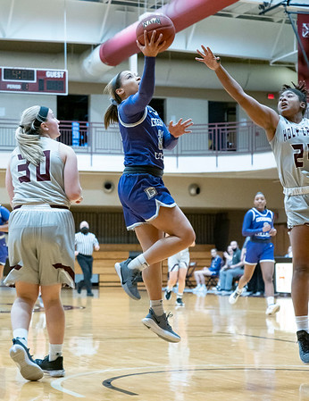 Goshen College guard Mariah Roe (22) shoots a basket against Holy Cross College forward Jaliah Nailor (24) during Wednesday's game at Holy Cross College in South Bend.