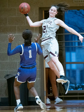 Holy Cross College forward Allison Hano (21) leaps to keep the ball inbounds during Wednesday's game at Holy Cross College in South Bend.