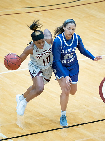 Holy Cross College guard Jayda Miller (10) dribbles the ball down court against Goshen College guard Mariah Roe (22) during Wednesday's game at Holy Cross College in South Bend.