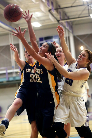 JAY YOUNG | THE GOSHEN NEWS<br /> Spring Arbor junior Autumn Goggin, center, out reaches teammate Rachel Nelson (33) and Goshen College junior Caitlyn O'Neal (20) for a rebound during their game Wednesday evening in Goshen.