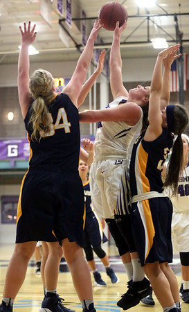 JAY YOUNG | THE GOSHEN NEWS<br /> Goshen College junior Caitlyn O'Neal, center, gets off a shot as she is squeezed between Spring Arbor defenders Rachel Driesenga (34) and Karly Bender during their game Wednesday evening in Goshen.