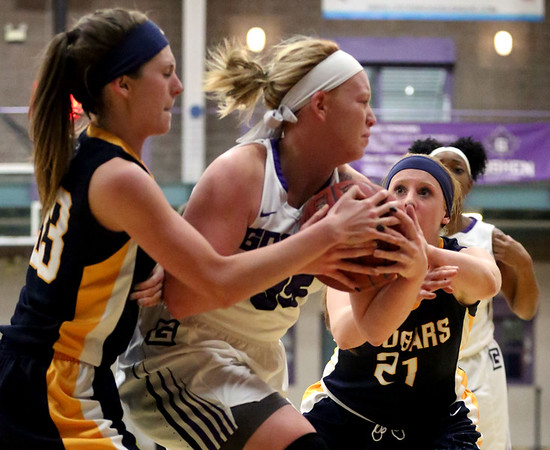 JAY YOUNG | THE GOSHEN NEWS<br /> Goshen College sophomore Sydney Stein, center, holds onto the ball with both hands as Spring Arbor defenders Rachel Nelson (33) and Kylie Townsley (21) try to rip the ball away during their game Wednesday evening in Goshen.