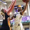 JAY YOUNG | THE GOSHEN NEWS<br /> Goshen College senior Lynnia Noel (23) hangs in the air as she shoots around Spring Arbor senior Rachel Driesenga (34) during their game Wednesday evening in Goshen.