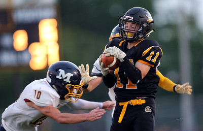 Black Rivers' Riley Gibbls brings in a pass between McDonald defenders Josh Celli (10) and Joe Celli during the second quarter. AARON JOSEFCZYK/GAZETTE