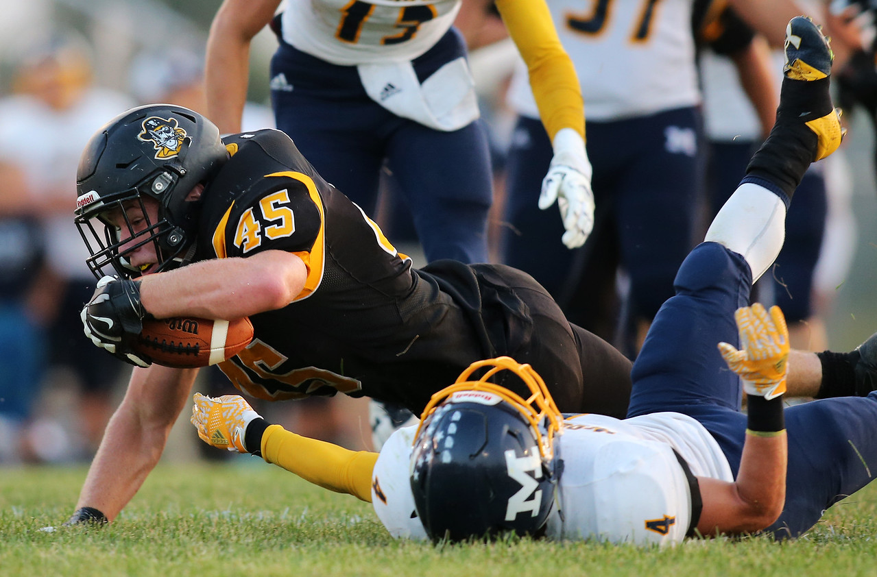 Black Rivers'  Jacob Campbell runs over McDonald defensive back Joe Celli on his way inside the 10 yard line during the second quarter. AARON JOSEFCZYK/GAZETTE