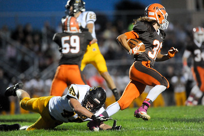 Buckeye's Keaton Sandor avoids the diving tackle of Black River's Jacob Campbell on a kick-off return in the first quarter Friday night at Buckeye. JUDD SMERGLIA / GAZETTE